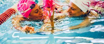 Two participants swim to the finish line at the OlymPINK Masters Sprint