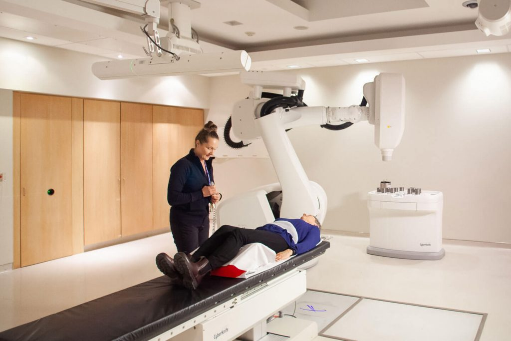 Julie Gratton with patient beside CyberKnife robot