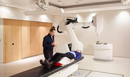 Julie Gratton with patient beside CyberKnife robot video thumbnail