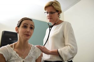 Dr. Jill Fulcher stands behind Stefany listening with stethoscope