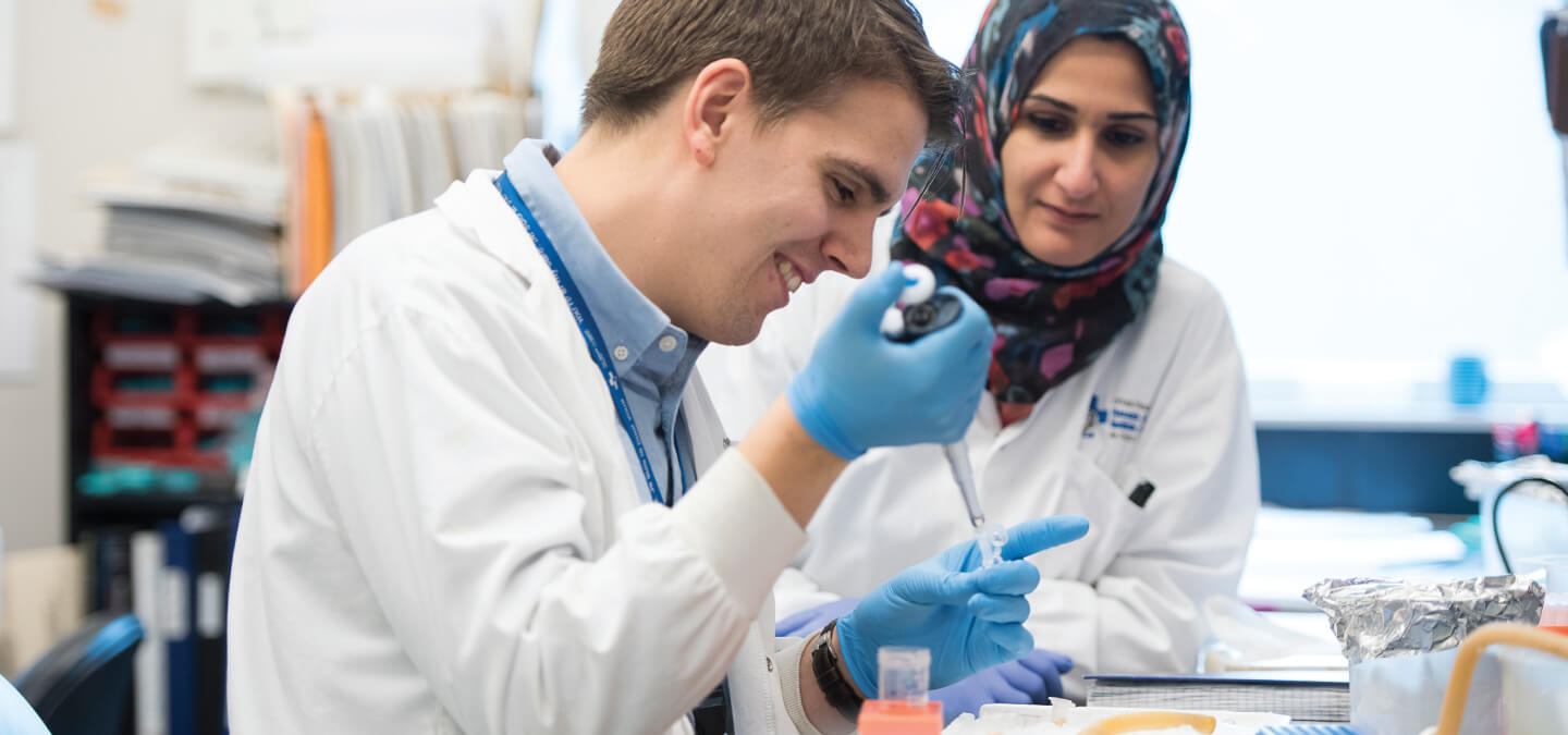 Two researchers work at a lab bench.