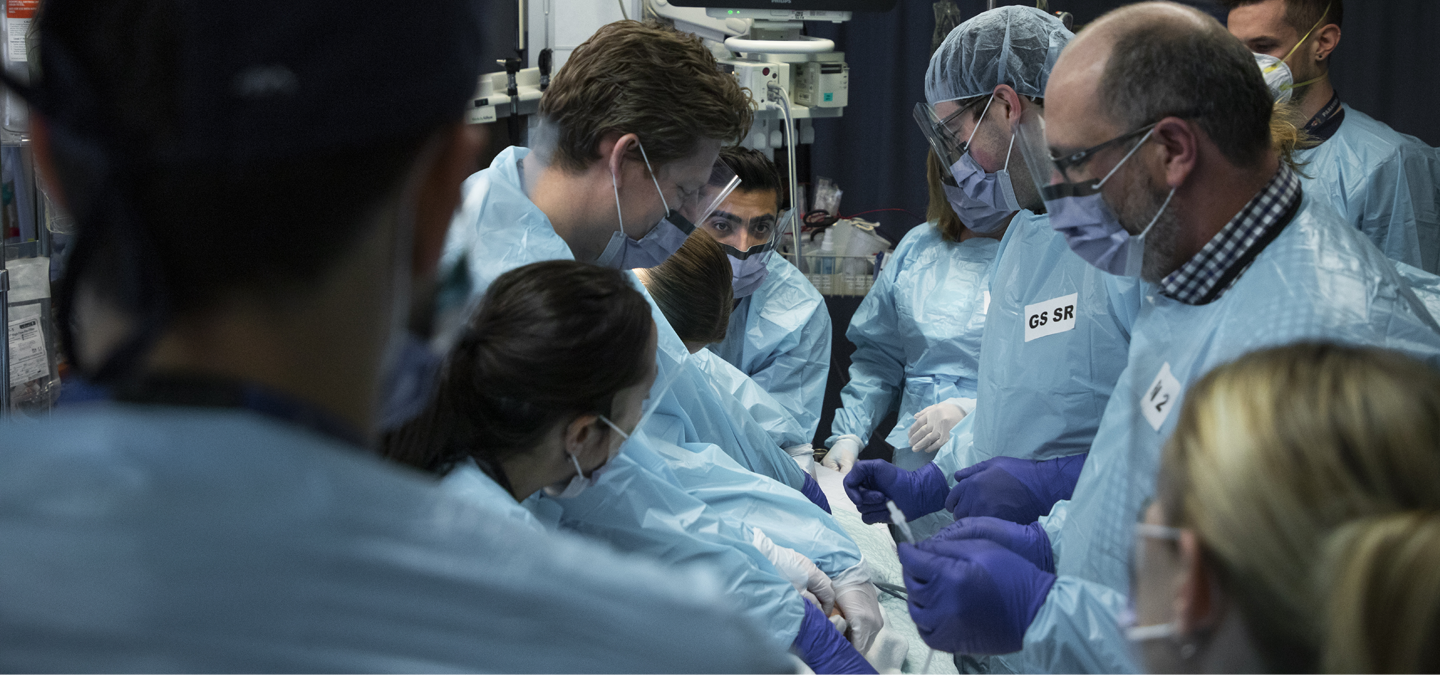 Hospital doctors and surgeons operating on a patient in a trauma bay